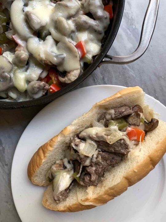 This is a picture of a philly cheesesteak skillet. There is a skillet full of philly cheesesteak, along with a plate with a hoagie and philly cheesesteak on the side.