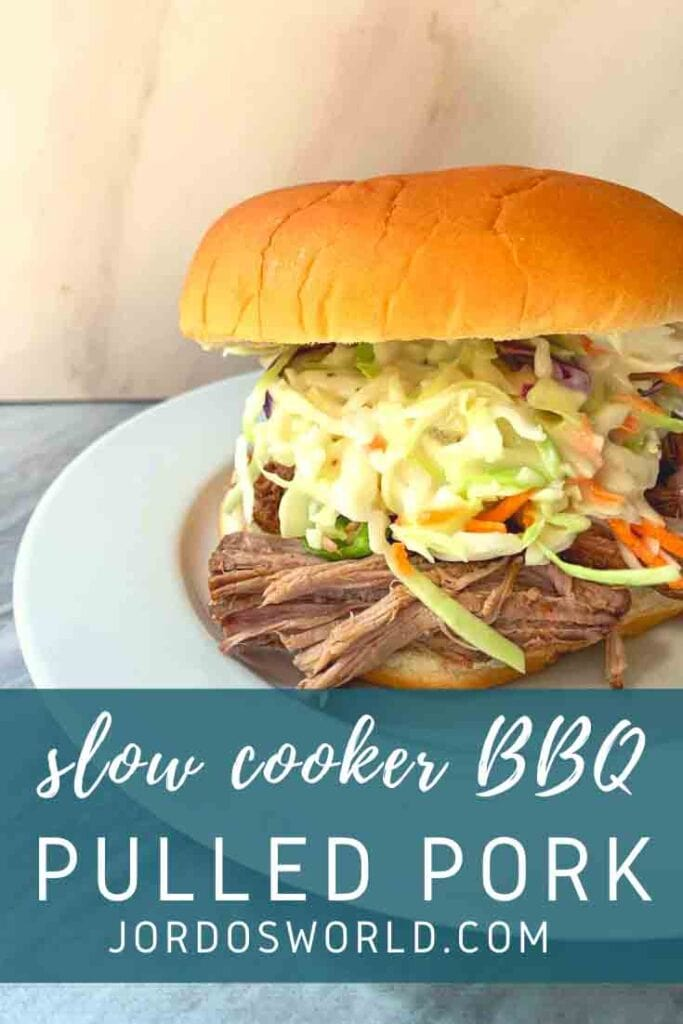 This is a Pinterest pin for slow cooker bbq pulled pork. There is a sandwich with a bun, coleslaw, and pulled pork sitting on a plate.