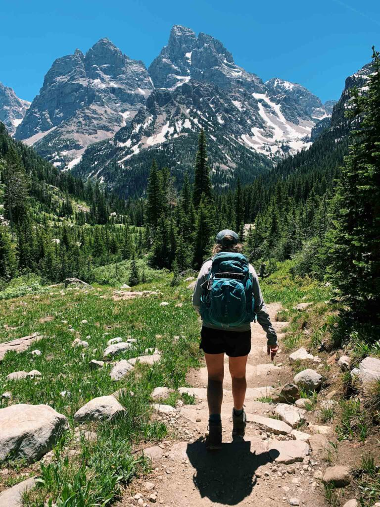 This is a picture of a girl hiking in grand teton national park. She has a blue backpack on and is walking on a trail towards the mountains.