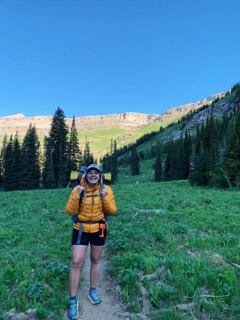 This is a picture of a girl hiking in grand teton national park. There is a girl in a yellow jacket and black shorts in a field with trees and mountains in the back.