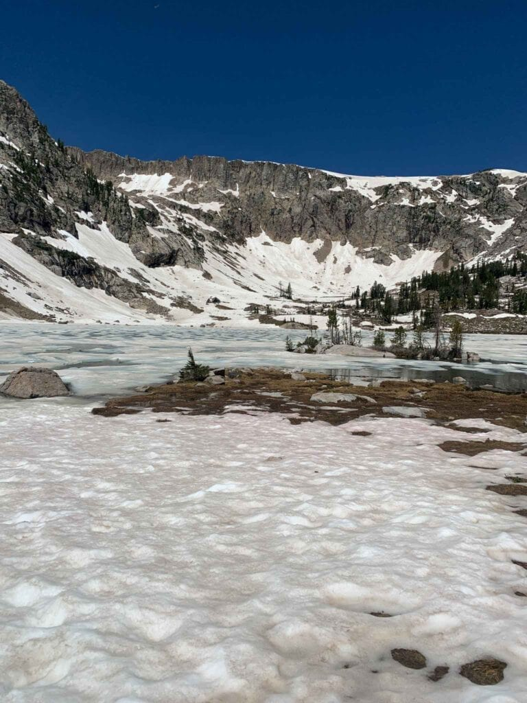 This is a picture of Solitude Lake in Grand Teton National Park. There is snow on the ground and the lake is still frozen over.