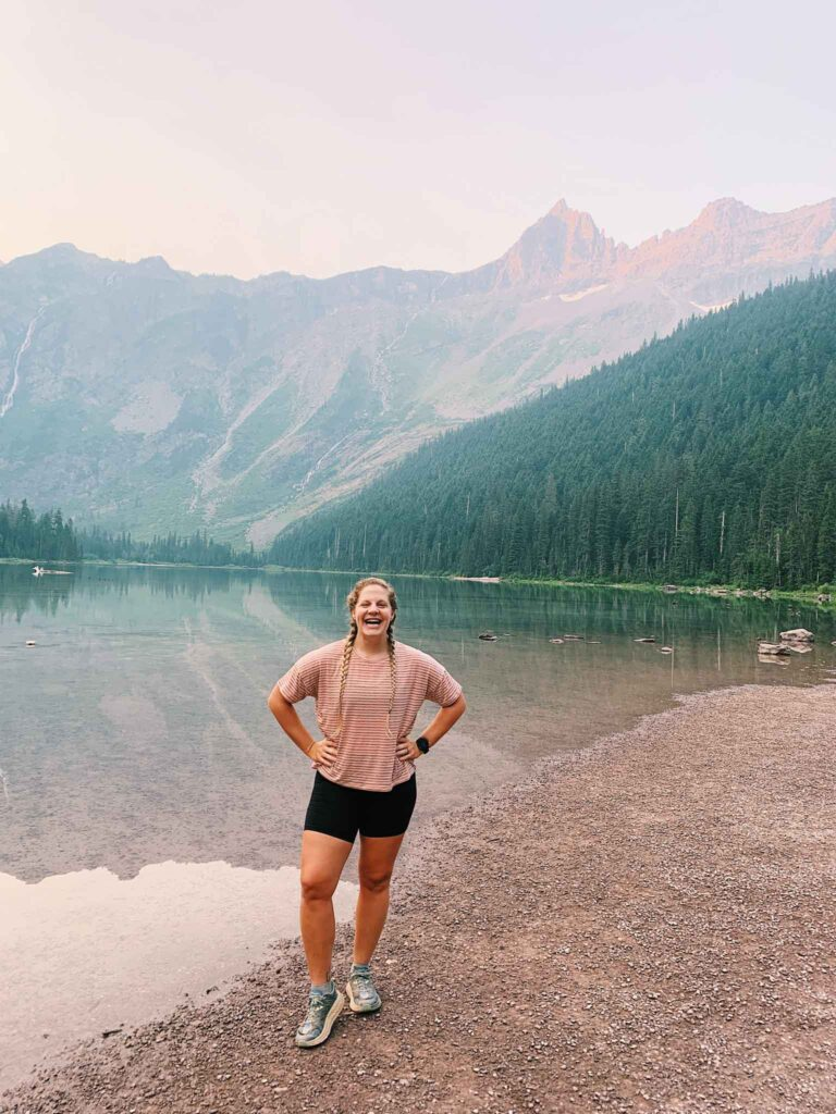 This is a girl in front of Avalanche Lake in Glacier National Park. There is a big reflective lake with green trees and a mountain in the back.