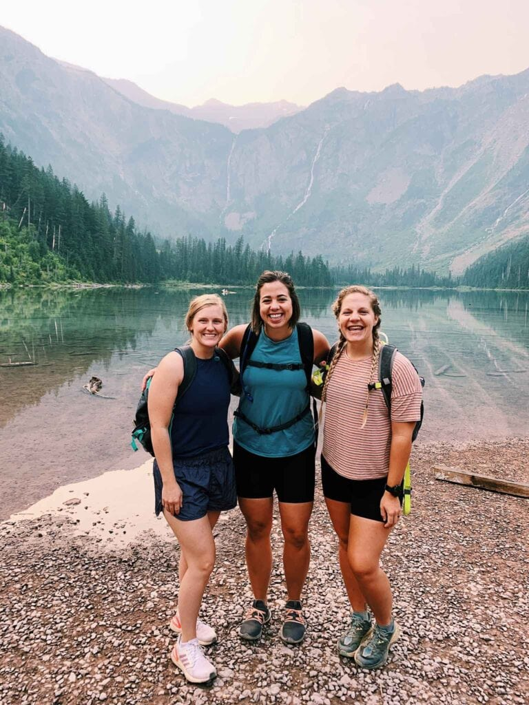 This is 3 girls in front of Avalanche Lake. There is a big lake with a sunrise and mountains behind them.