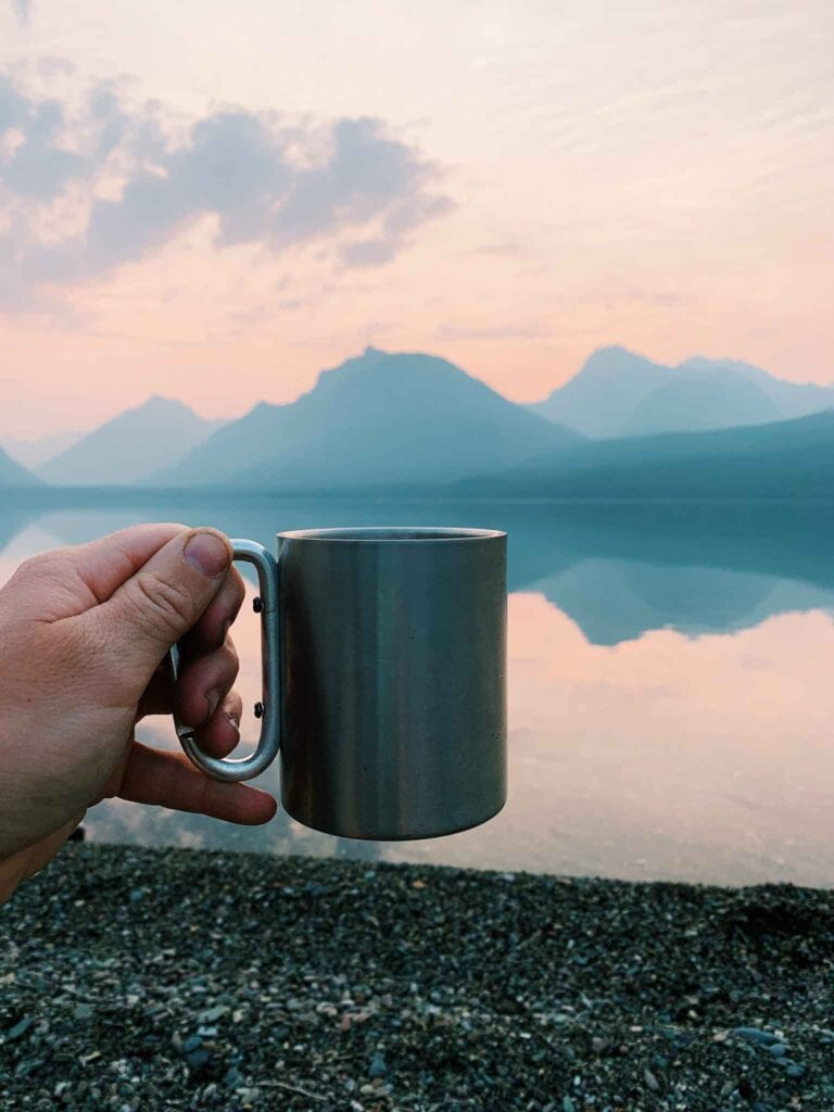 This is a picture of a cup of coffee at sunrise in glacier national park with mcdonald lake.