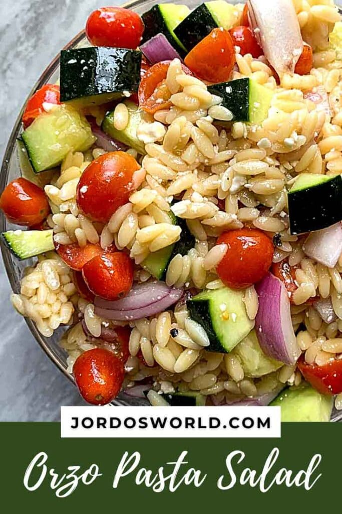 This is a pinterest pin for orzo pasta salad. There is a big glass bowl filled with orzo, cucumbers, tomatoes, red onions, feta cheese, and dressing.