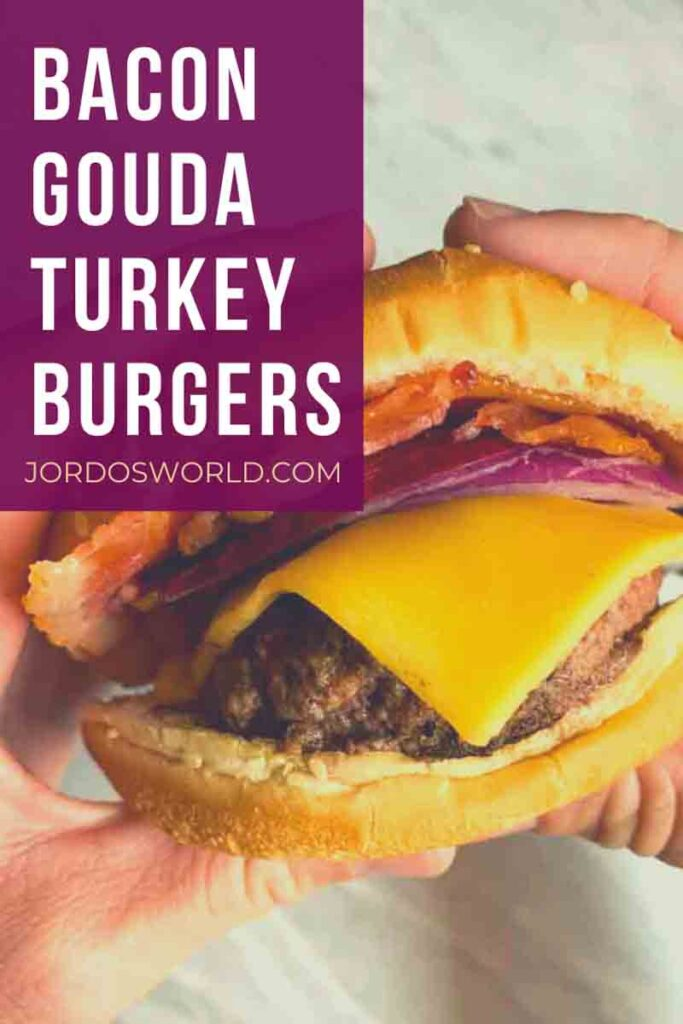 This is a pinterest pin for a bacon gouda turkey burger. There are two hands holding a bun, slices of bacon, red onion, and a burger patty with melted cheese.