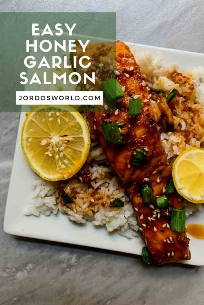 This is a plate of honey garlic salmon. There is a white plate topped with rice and a piece of honey garlic salmon. The salmon is dark red, covered in sauce, and topped with lemon, green onion, and sesame seeds.