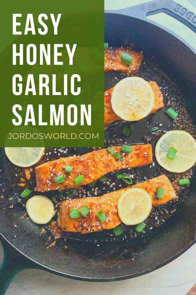 This is a pinterest pin for honey garlic chicken. There is a cast iron skillet filled with salmon filets, sauce, and topped with lemon slices and green onions.