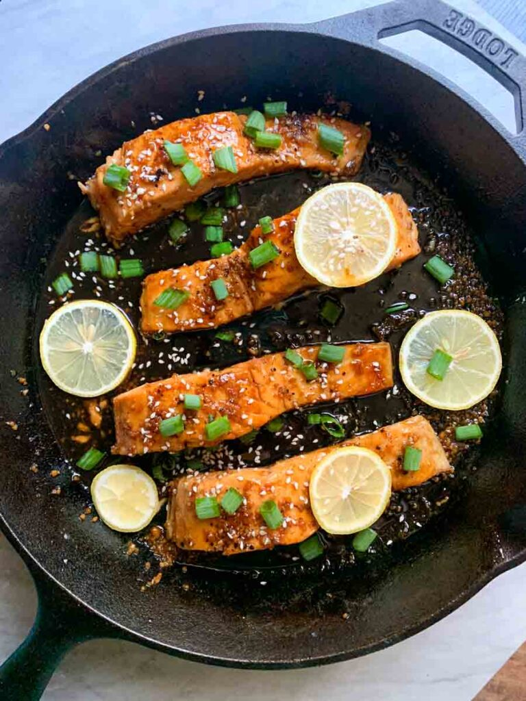 This is a skillet of honey garlic salmon. There are 4 salmon filets covered with sauce, green onions, sesame seeds, and lemon slices.