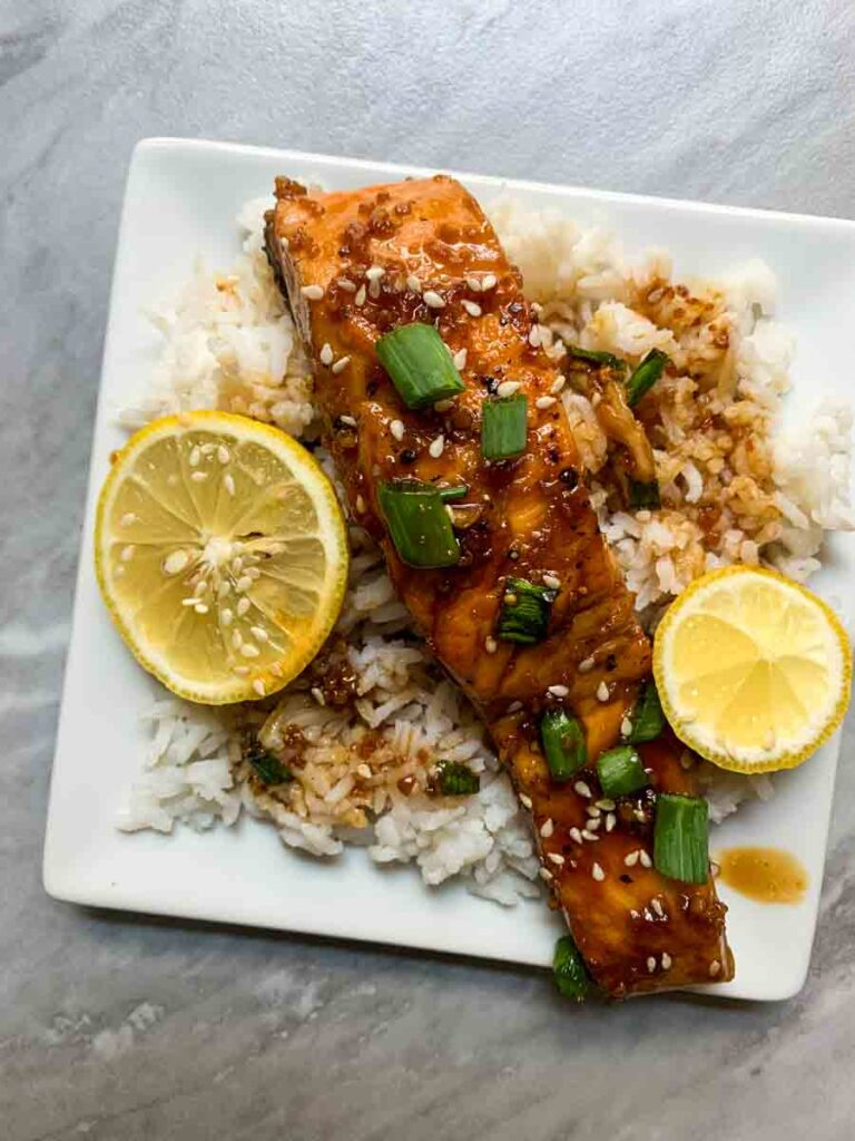This is a plate of garlic honey salmon. There is white rice topped with a piece of saucy red salmon sprinkled with sesame seeds, chopped green onions, and slices of salmon.