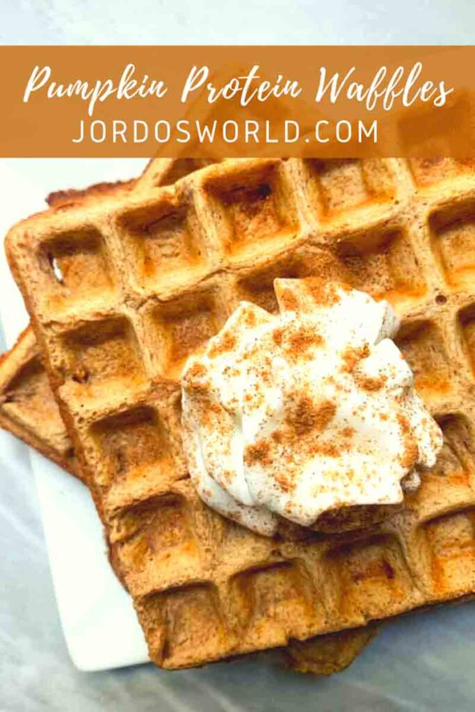 This is a pinterest pin for pumpkin protein waffles. There is a plate of light brown waffles topped with whipped cream and sprinkled with cinnamon.