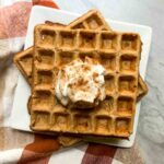 This is a plate of pumpkin protein waffles. The waffles are light brown, topped with whipped cream, and sprinkled with cinnamon.